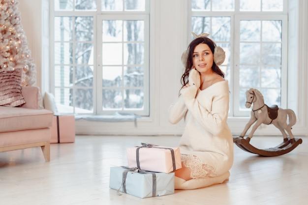 Belle jeune femme en robe blanche posant avec des coffrets cadeaux