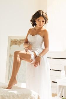 Belle jeune femme en robe blanche se préparant au jour du mariage et mettant la jarretière sur sa jambe. détails du matin de la mariée.