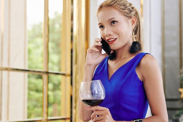 Belle jeune femme en robe de cocktail buvant du vin rouge et parlant au téléphone avec un ami ou un petit ami