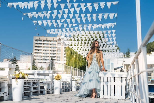 Belle jeune femme en robe debout sur la jetée