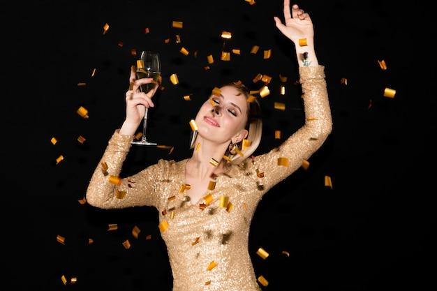 Belle jeune femme en robe élégante danse à la fête avec flûte de champagne en tombant des confettis dorés avec ses mains levées