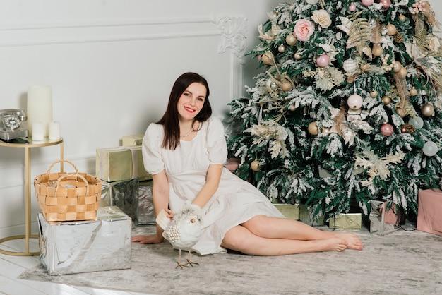 Belle jeune femme en robe élégante debout à côté de l'arbre de noël et des cadeaux.