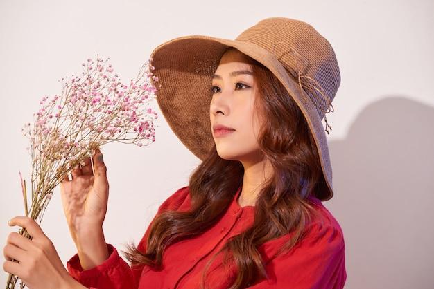 Une belle jeune femme en robe d'été et chapeau de paille posant tout en tenant des fleurs de bouquet