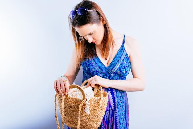 Belle jeune femme en robe d'été et lunettes violettes regardant à l'intérieur du sac nerveux. concept perte de clés ou vol de portefeuille sur fond blanc