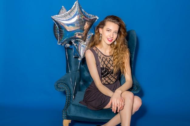 Belle jeune femme en robe grise assise sur un fauteuil bleu avec des ballons d'argent
