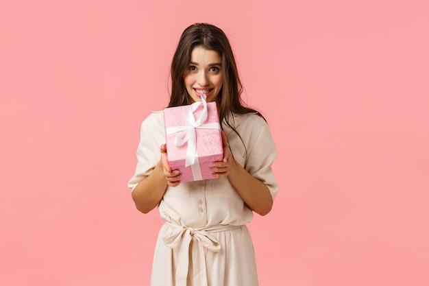 Belle jeune femme en robe légère élégante, boîte-cadeau mordante et souriant, voulant ouvrir, tentant de voir ce qui est à l'intérieur du cadeau surprise, fond rose