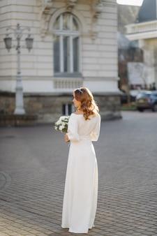 Belle jeune femme en robe de mariée posant dans la rue en ville