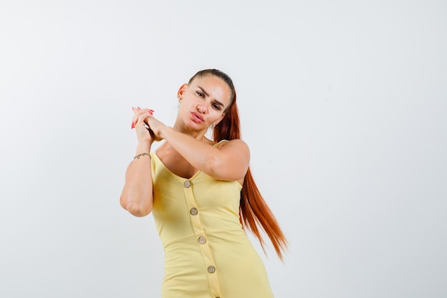 Belle jeune femme en robe montrant le geste des armes à feu et regardant pensif, vue de face.