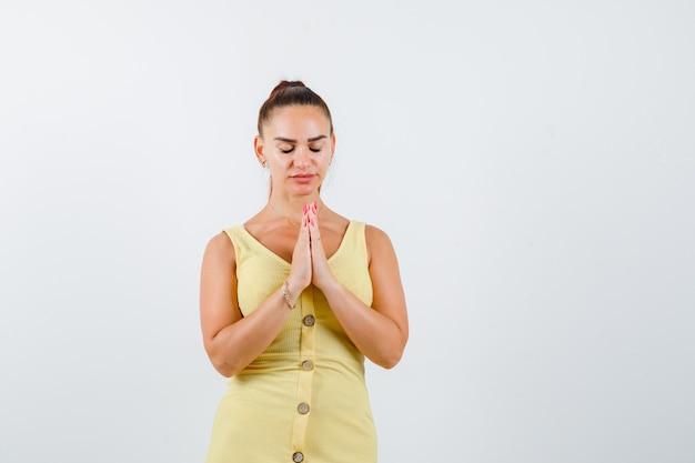 Belle jeune femme en robe montrant le geste de namaste et à la recherche focalisée, vue de face.