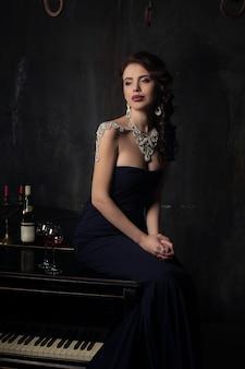 Belle jeune femme en robe noire à côté d'un piano avec des bougies candélabres et du vin, atmosphère sombre et dramatique du château. bohême.