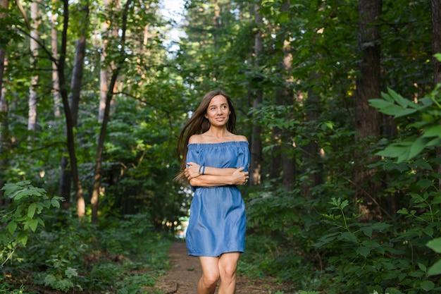 Belle jeune femme en robe qui court dans la forêt d'été