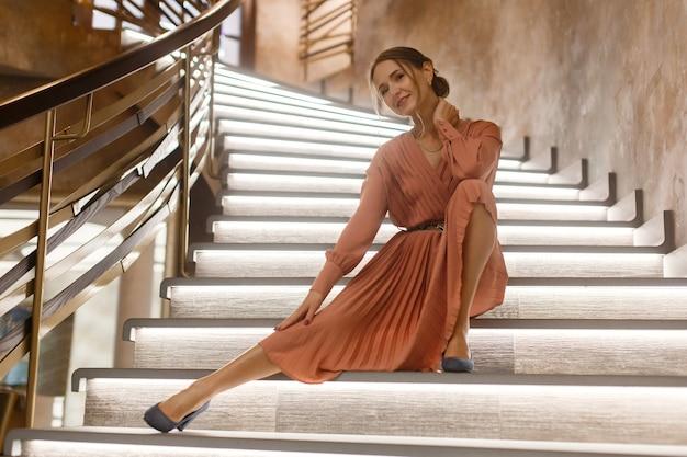 Belle jeune femme en robe rose assise dans les escaliers portrait de beauté d'intérieur femme heureuse souriante