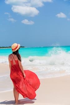 Belle jeune femme en robe rouge au bord de mer tropicale