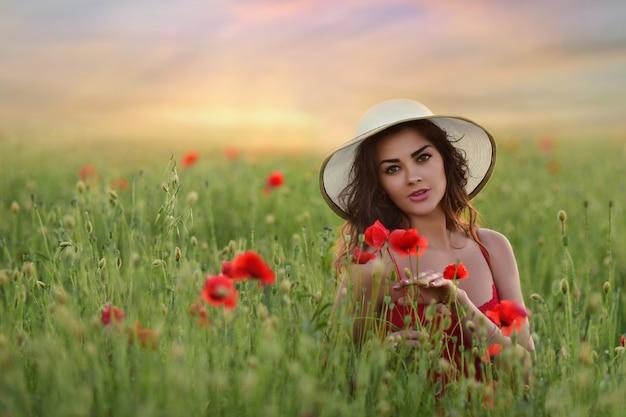 Belle jeune femme en robe rouge et chapeau blanc se promène sur le terrain avec des coquelicots