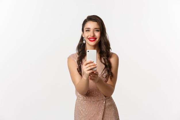 Belle jeune femme en robe de soirée et maquillage, prenant des photos sur smartphone, vous tirant sur l'appareil photo du téléphone, debout sur fond blanc.