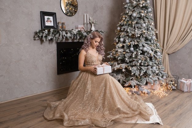 Belle jeune femme en robe de soirée près de l'arbre de noël décoré
