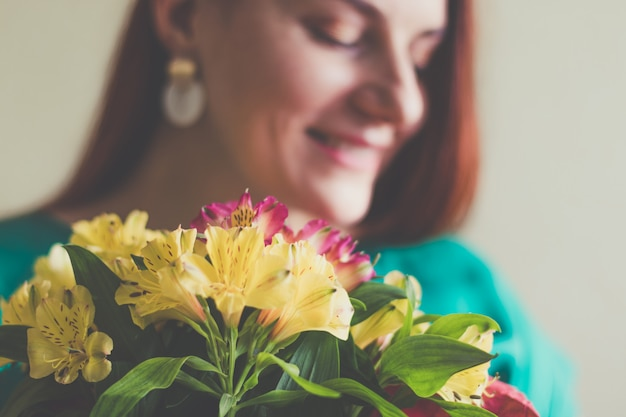 Belle jeune femme en robe verte tenant un bouquet de fleurs de printemps