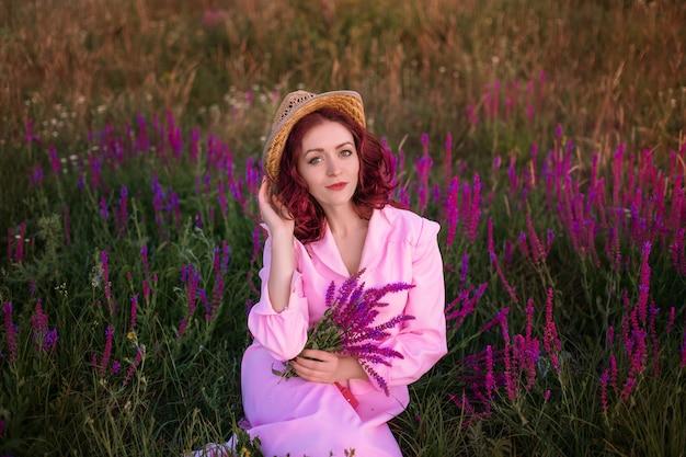 Belle jeune femme en robe vintage rose et chapeau de paille dans le champ fleurs sauvages (sauge, salvia)