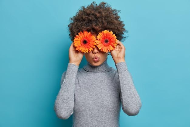 Belle jeune femme romantique avec des fleurs devant les yeux, garde les lèvres arrondies, tient la marguerite orange gerbera