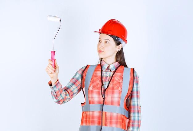 Belle jeune femme avec un rouleau à peinture pour peindre la réparation de mur.