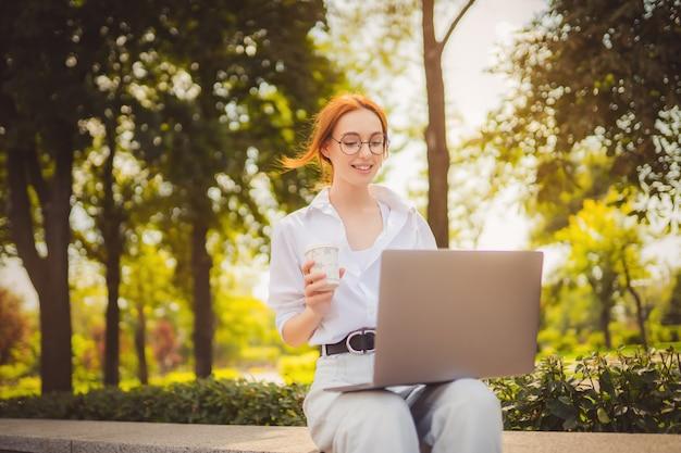 Belle jeune femme rousse assise dans le parc et utilisant un ordinateur portable étudiant universitaire indépendant porter...