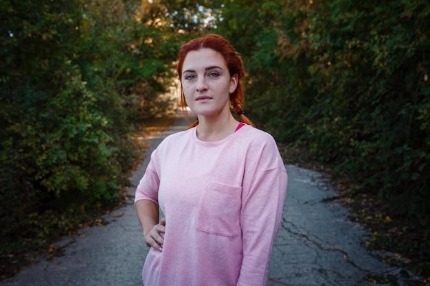 Belle jeune femme rousse dans la forêt d'automne. idée et concept de temps libre, de bonheur, de soins et de liberté, d'activités de plein air et d'un mode de vie sain