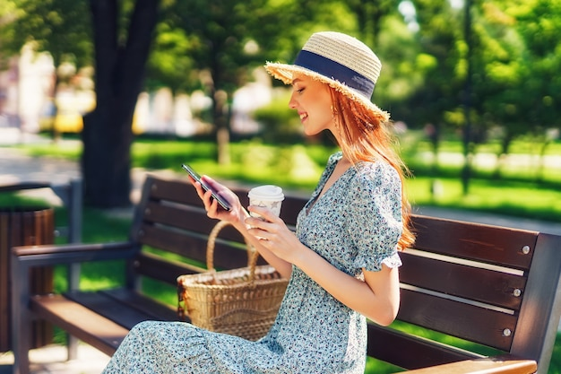 Belle jeune femme rousse se détendre sur le banc du parc de la ville tenant un café dans les mains à l'aide de p...