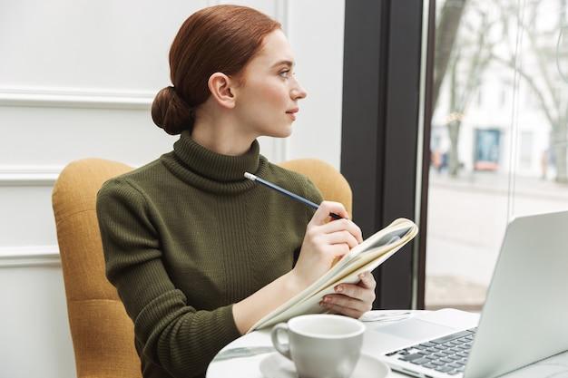 Belle jeune femme rousse se reposant à la table du café à l'intérieur, buvant du café, travaillant sur un ordinateur portable