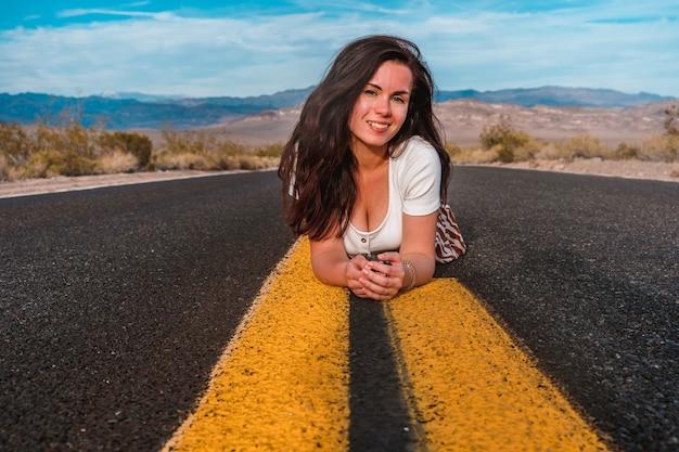 Belle jeune femme sur une route à ruelle jaune au milieu de death valley usa