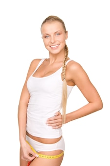 Belle jeune femme avec ruban à mesurer sur blanc