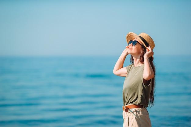Belle jeune femme s'amusant sur le bord de la mer tropicale