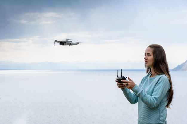 Belle jeune femme s'amusant avec un mini drone à l'extérieur. la fille se tient contre le lac d'eau
