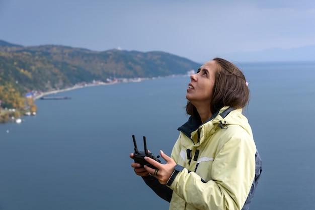 Belle jeune femme s'amusant avec un mini drone à l'extérieur.