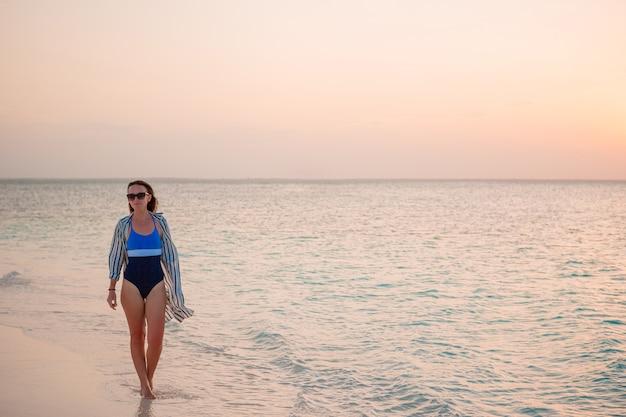 Belle jeune femme s'amuser au bord de mer tropical.