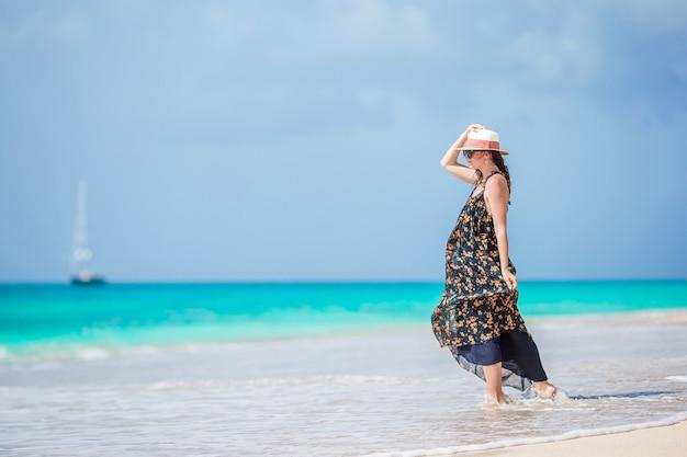 Belle jeune femme s'amuser au bord de la mer tropicale. fille heureuse, marchant sur la plage tropicale de sable blanc