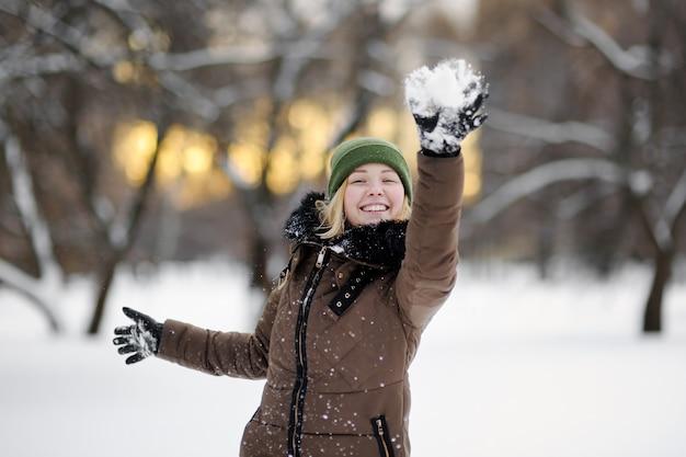Belle jeune femme s'amuser dans le parc d'hiver