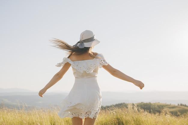 Belle jeune femme s'amuser à l'extérieur des montagnes de fond de nature.