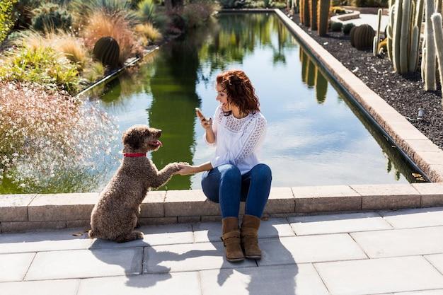 Belle jeune femme s'amuser avec son mignon chien brun et prendre une photo avec téléphone portable. amour pour les animaux concept. en plein air