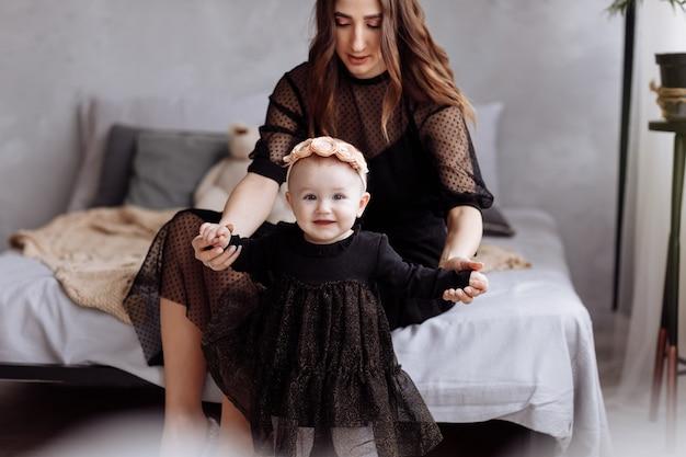 Belle jeune femme et sa charmante petite fille s'étreignent et sourient sur le lit