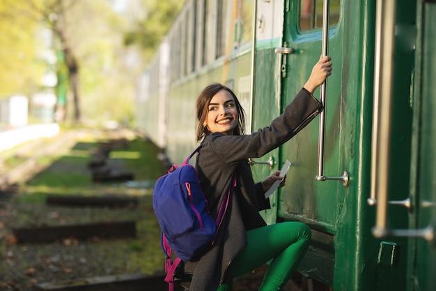 Belle jeune femme avec sac à dos aller voyager en train à la gare.