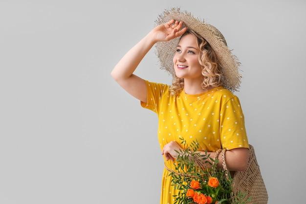 Belle jeune femme avec sac et fleurs sur gris