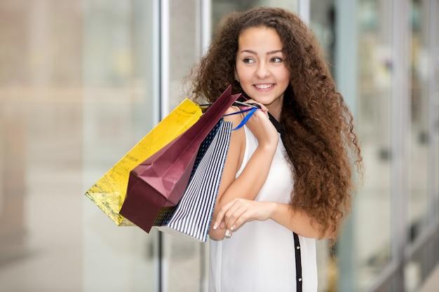Belle jeune femme avec des sacs à provisions dans le centre commercial