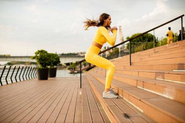 Belle jeune femme sautant dans les escaliers au bord de la rivière