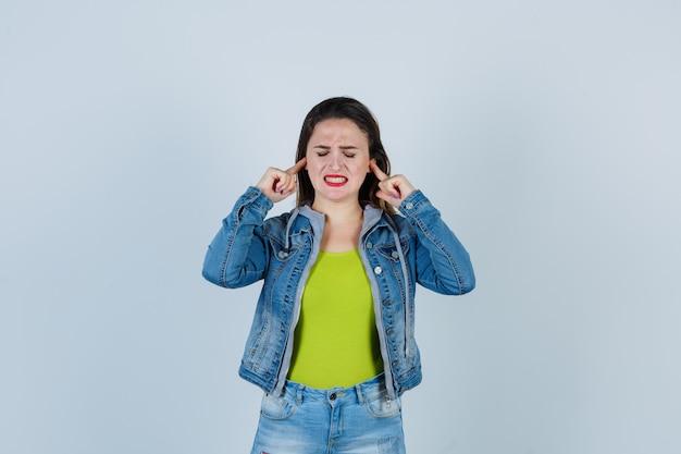 Belle jeune femme se bouchant les oreilles avec les doigts en tenue de denim et l'air agacée. vue de face.