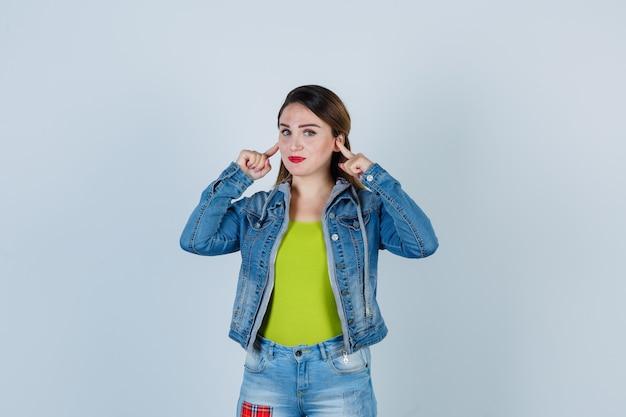 Belle jeune femme se bouchant les oreilles avec les doigts en tenue de denim et semblant raisonnable. vue de face.