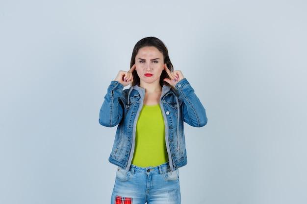 Belle jeune femme se bouche les oreilles avec les doigts en tenue de denim et a l'air de s'ennuyer. vue de face.