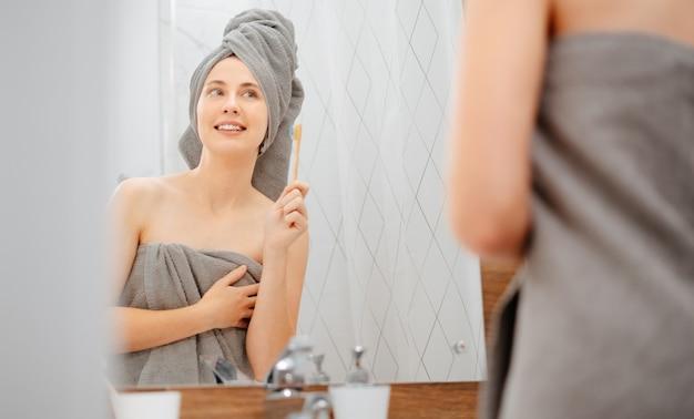 Belle jeune femme se brosse les dents devant le miroir de la salle de bain. concept de dentisterie et de soins buccaux.