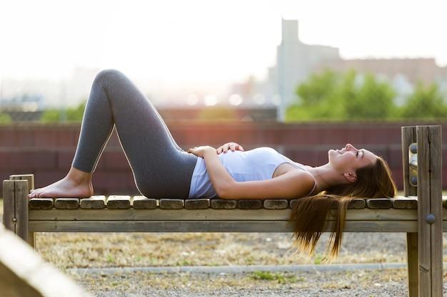 Belle jeune femme se détendant dans le parc.