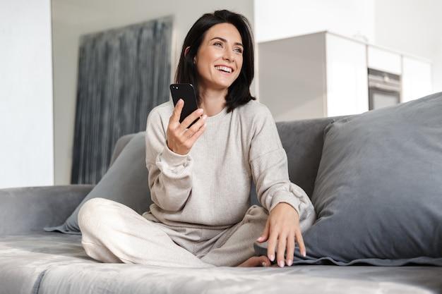Belle jeune femme se détendre sur un canapé à la maison, à l'aide de téléphone mobile