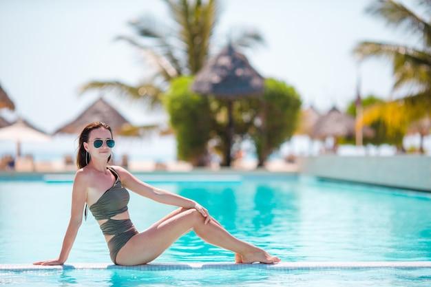 Belle jeune femme se détendre dans la piscine infiniti à l'hôtel de luxe